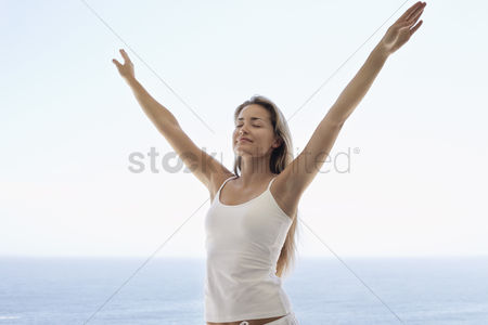 Smiling : Young woman with arms outstretched and eyes closed on beach