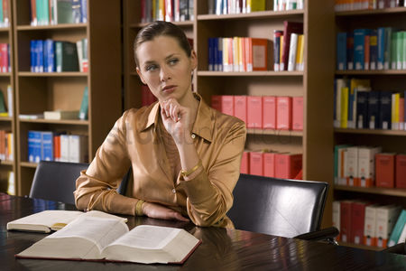 University : Young woman with book working at desk in library