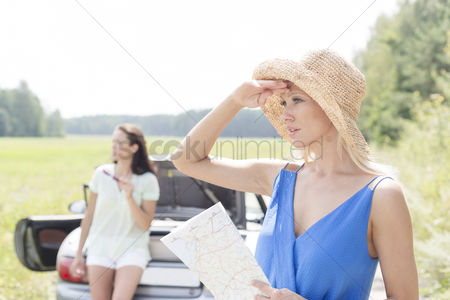 On the road : Young woman with map looking away while friend leaning on convertible in background