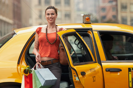 Car : Young woman with shopping bags exiting yellow taxi cab