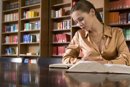 University : Young woman writing at desk in library