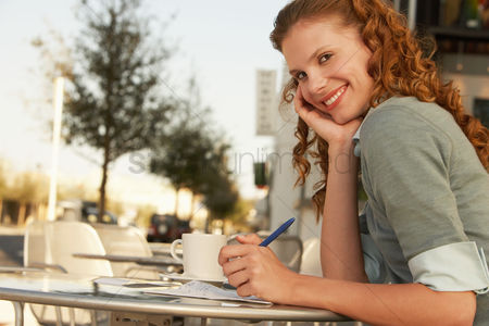Food  beverage : Young woman writing at outdoor cafe portrait
